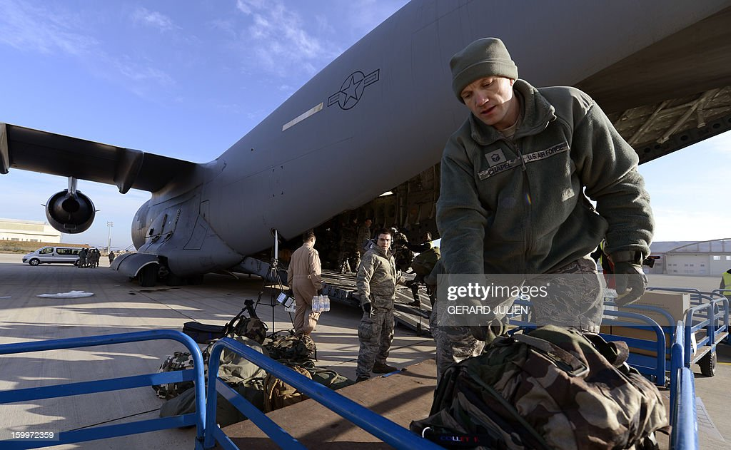 US soldier carry French equipment on board a C17 aircraft of the US Airforce carriying French armoured vehicles at the Istres military airport (BA 125) on January 24, 2012 in Istres, southern France, prior to take off and heading toward Mali as part of the 'Serval' operation.