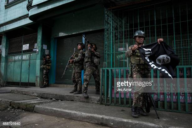 A soldier carrying a captured ISIS flag while clearing a city street of militants on May 26 2017 in Marawi city southern Philippines Filipino...