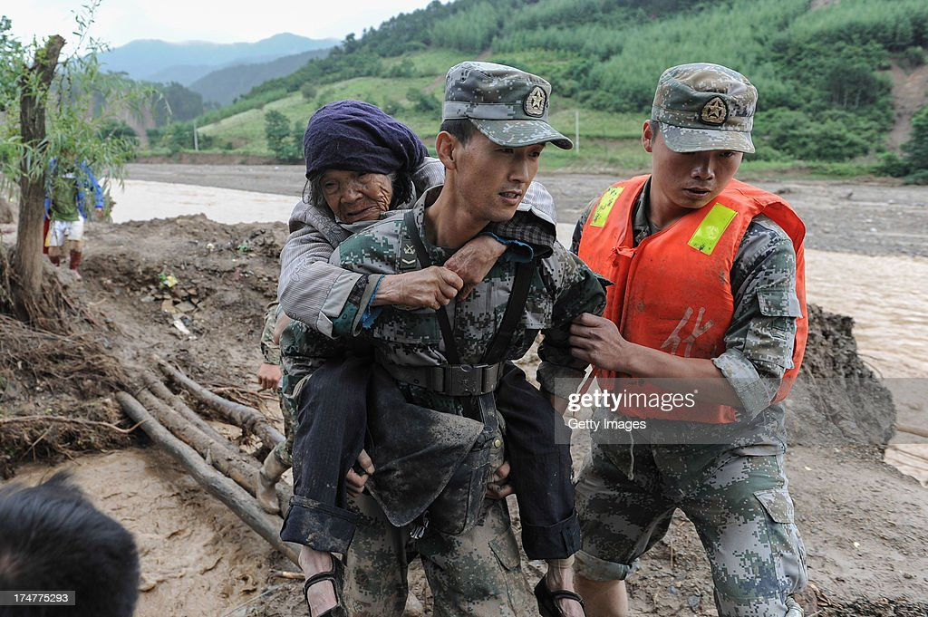 A soldier carrying an old woman heads to a shelter on July 28, 2013 in Tianshui, China. At least 22 people were killed and three others missing after rainstorm-triggered floods and landslides hit many places of Tianshui city recently.