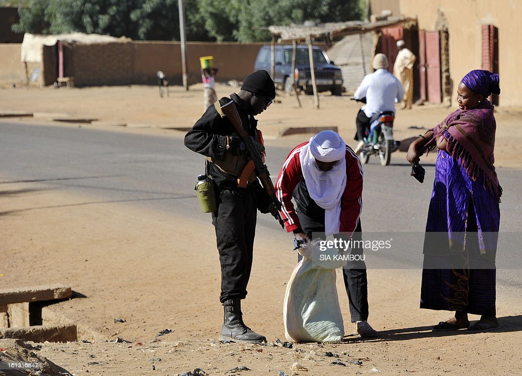 A soldier checks the back of a pedestrian on February 7, 2013 during reinforced security patrols of Gao. A massive explosion was heard near Gao in northern Mali late Saturday, hours after villagers near the city detained two youths preparing for suicide bombings. AFP PHOTO / SIA KAMBOU