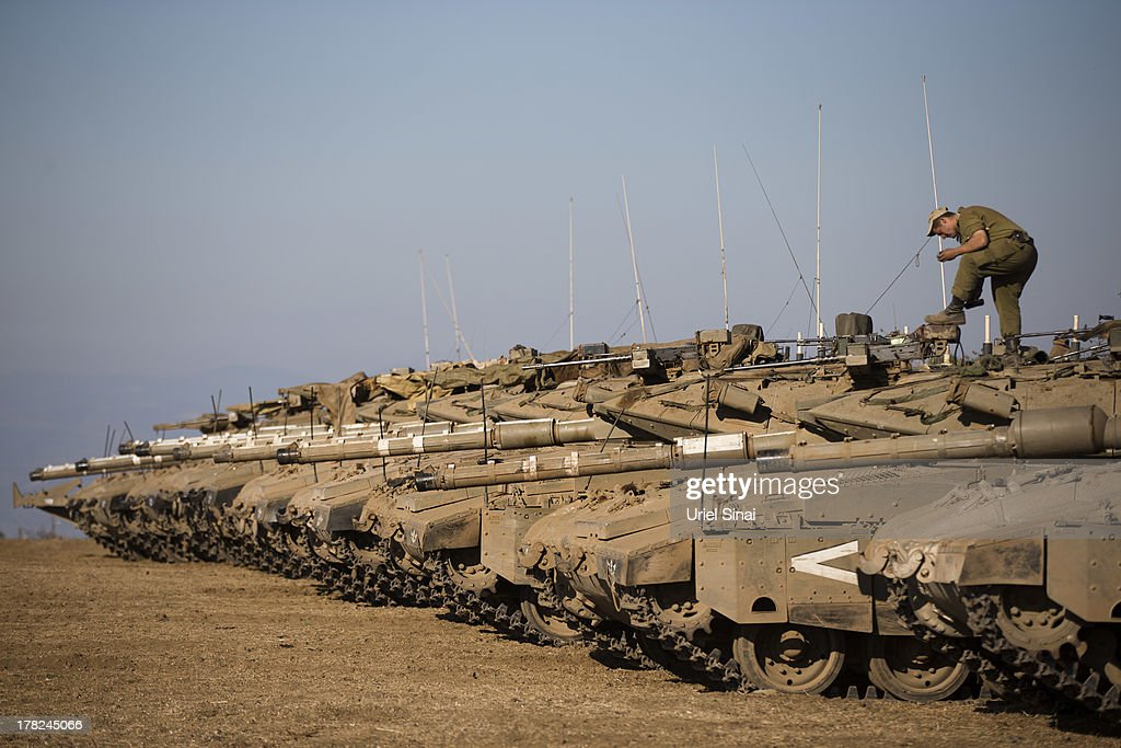 A soldier cleans his shoos on top of a tank as Israeli troops take part in a military exercise on August 28, 2013 near the border of Syria, in the Israeli-annexed Golan Heights. Tension rises in Israel amid international talks of a military intervention in Syria.