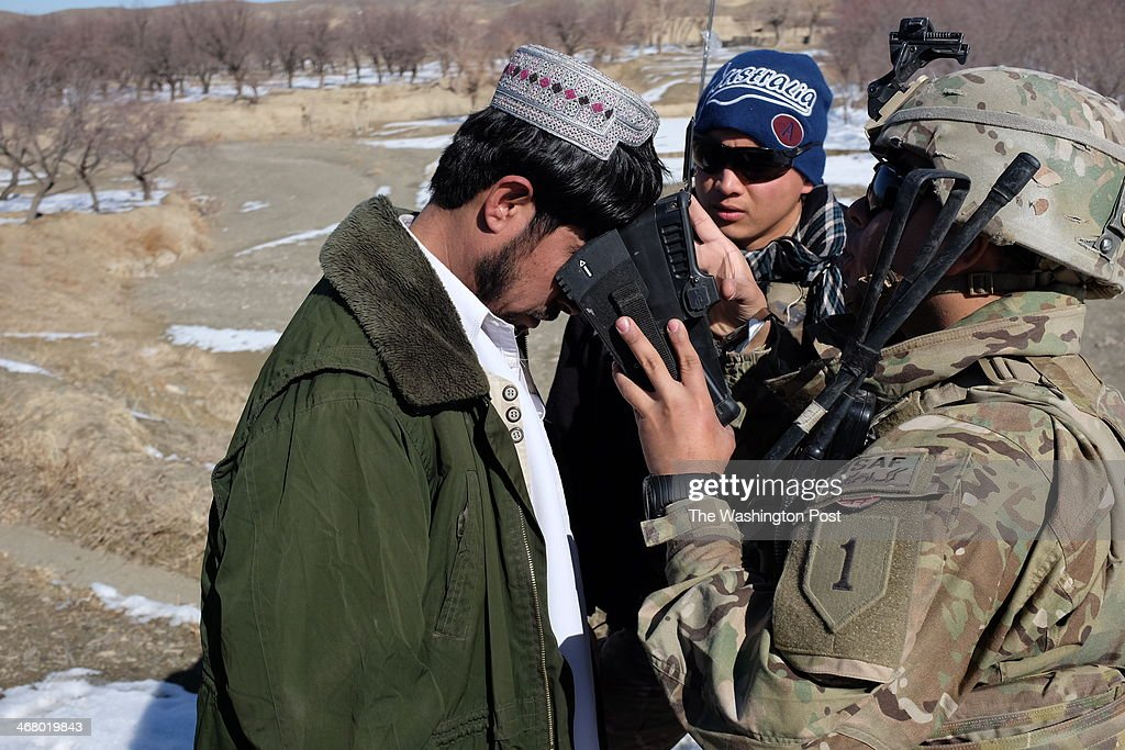 A US soldier conducts a biometric test of a local man in Nabahar district of Zabul Province, Afghanistan on January 17, 2014. The operation was intended to bring security to remote, restive parts of the country before this spring's election.