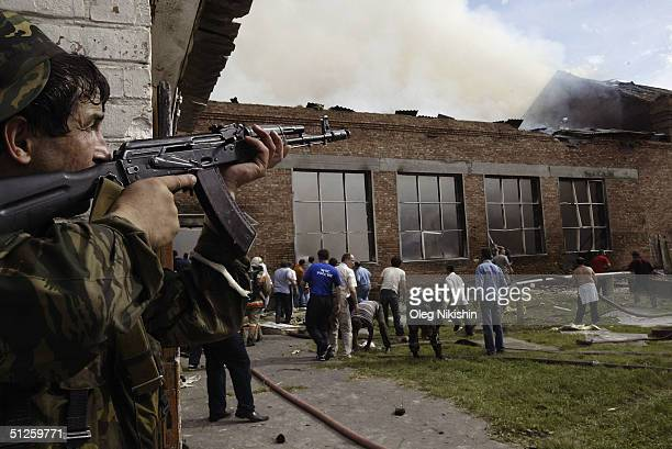 A soldier covers the roof as volunteers survey the area after special forces stormed a school seized by Chechen separatists on September 3 2004 in...