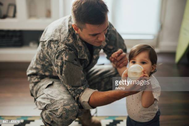 Soldier dad holding bottle for his little girl