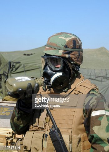 A soldier drinks water from a canteen while wearing a gas mask. : Stock Photo