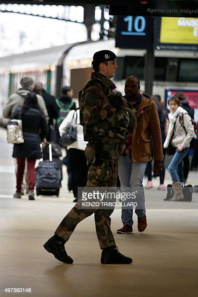 A soldier enforcing the Vigipirate plan France's national security alert system patrols as commuters and travellers walk through the Gare du Nord...