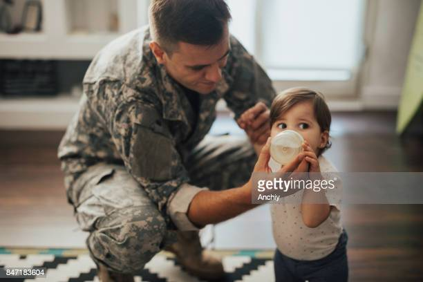US soldier feeding his baby girl