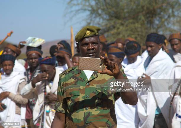 Soldier filming with his mobile phone during the Gada system ceremony in Borana tribe Oromia Yabelo Ethiopia on March 7 2017 in Yabelo Ethiopia
