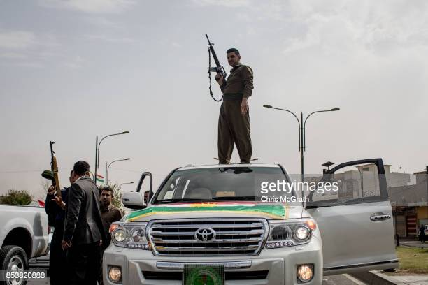 A soldier fires his gun in the air to celebrate the referendum on the road outside a voting station on September 25 2017 in Kirkuk Iraq Despite...