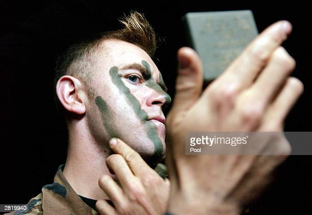 S soldier from 18 3rd Brigade of the 4th Infantry Division applies camouflage face paint before going on a mission December 17 2003 in Samarra Iraq A...