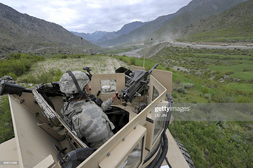 A US soldier from 1st Infantry Division keeps a lookout on a passing convoy from the gunner's position of an MRAP vehicle in Nishagam in...