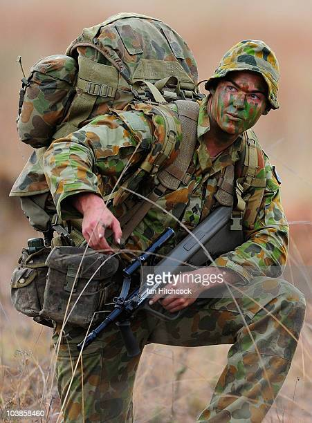 A soldier from 3 RAR kneels to receive orders after a paratroop drop during an airborne combat team exercise as part of a combined Arms training...