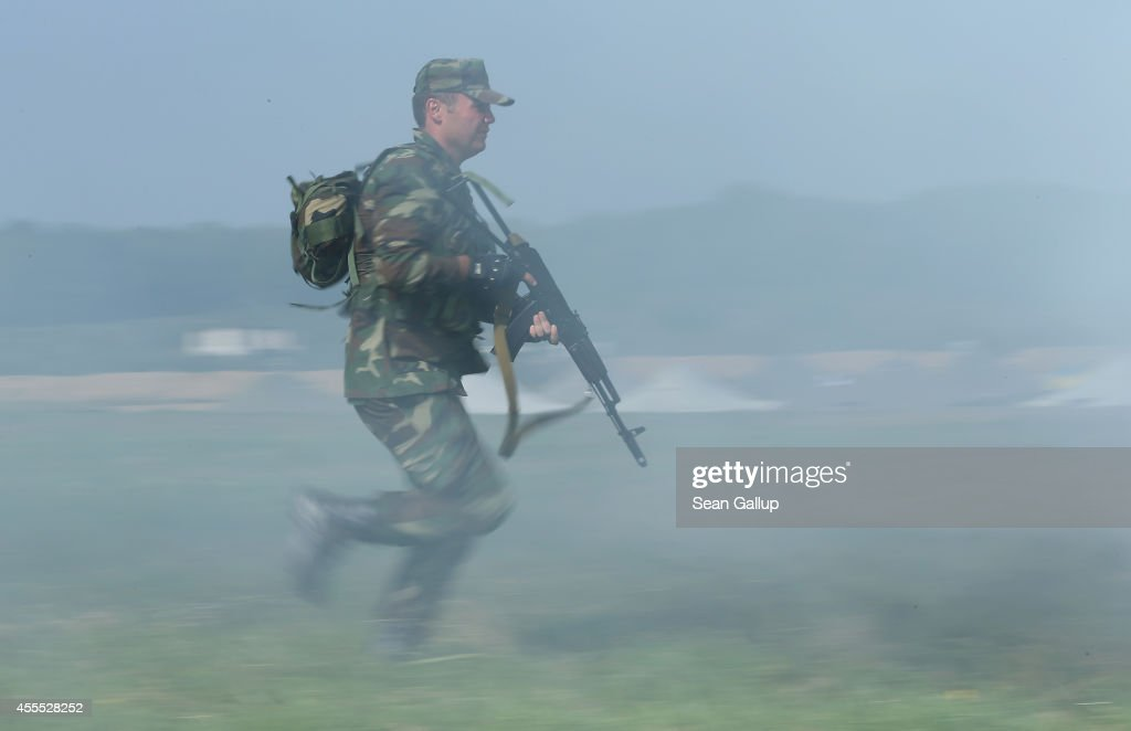 A soldier from Azerbaijan advances through smoke during training on the second day of the 'Rapid Trident' bilateral military exercises between the...