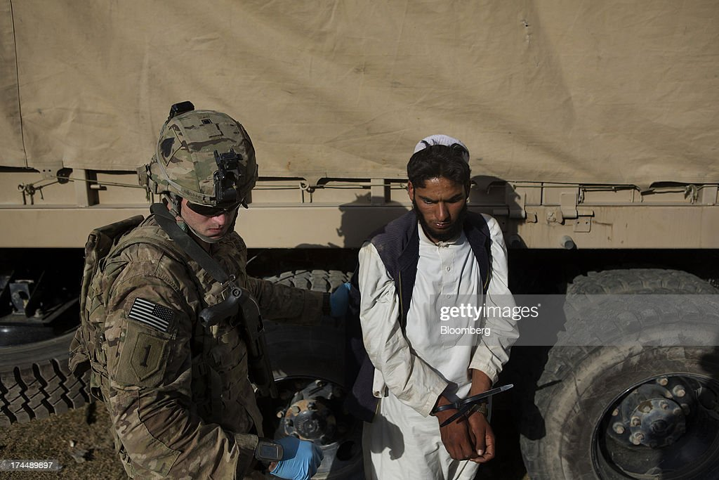 A soldier from Easy Co. of the 2-506th Infantry Battalion of the 4th Brigade of the 101st Airborne Division registers a detainee in a biometric system as they conduct a mission with the Afghan National Army and Police in the remote Musa Khel district of Khost province, Afghanistan, on Thursday, July 4, 2013. U.S. President Barack Obama has maintained his position of ending U.S. combat in Afghanistan by the end of next year, though that plan has included keeping in place several thousand troops for support. Photographer: Victor J. Blue/Bloomberg via Getty Images