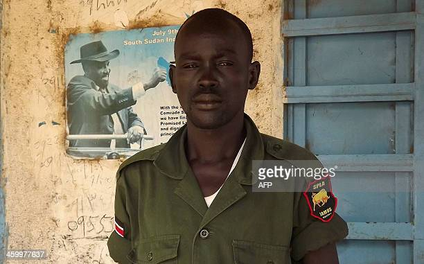 A soldier from South Sudan's army poses in front of a poster of President Salva Kiir in Malakal in the Upper Nile State of South Sudan on December 31...