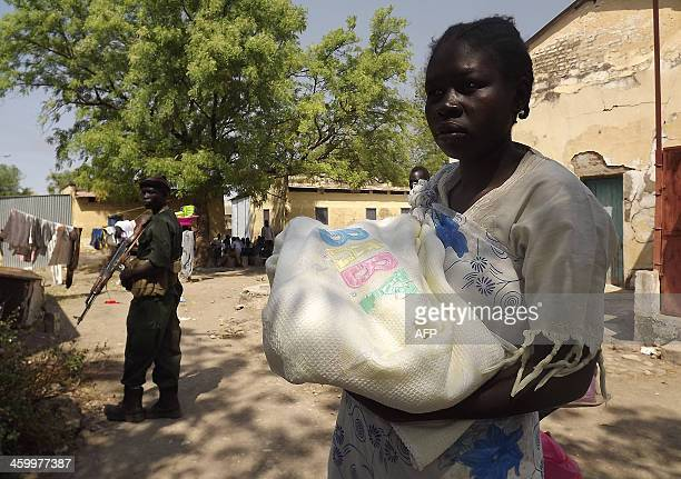 A soldier from South Sudan's army stands guard as a woman walks by in Malakal the Upper Nile State of South Sudan on December 31 2013 South Sudan's...