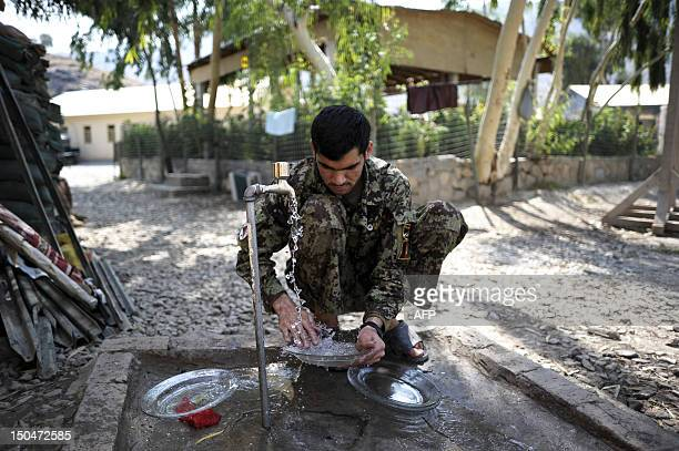 A soldier from the 2nd Kandak 2nd Brigade 201st corps of the Afghan National Army washes a plate to serve food for celebrating Eide fitr inside...