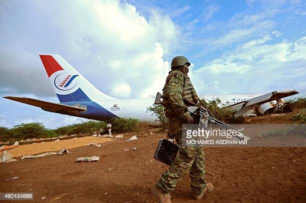 A soldier from the African Union peacekeeping force stands guard at the site where a cargo plane carrying supplies for AU troops crashlanded outside...