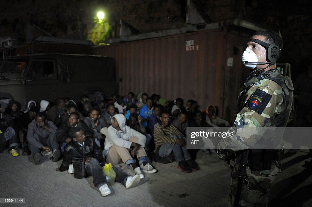 A soldier from the Armed forces of Malta watches over a group of migrants shortly after they were rescued and brought ashore to the Armed Forces of Malta Maritime base in Haywharf, on November 9, 2012 in Valletta. The Maltese military rescued 250 undocumented migrants believed to be Eritrean from a stricken boat, officials said, after reports the vessel had been adrift for days. AFP PHOTO/Matthew Mirabelli -MALTA