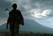 A soldier from the Democratic Republic of Congo regular army stands guard in Kibati near Goma with the Nyiragongo Volcano in the background on...