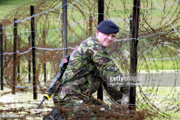 A Soldier from the Devonshire and Dorset regiment tightens razor wire in the fields surrounding Drumcree Church Portadown Co Armagh The Orange church...