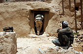 June 4, 2005 - A soldier from the National Guard stoops to enter and search the home of a suspected Taliban member in Afghanistan.