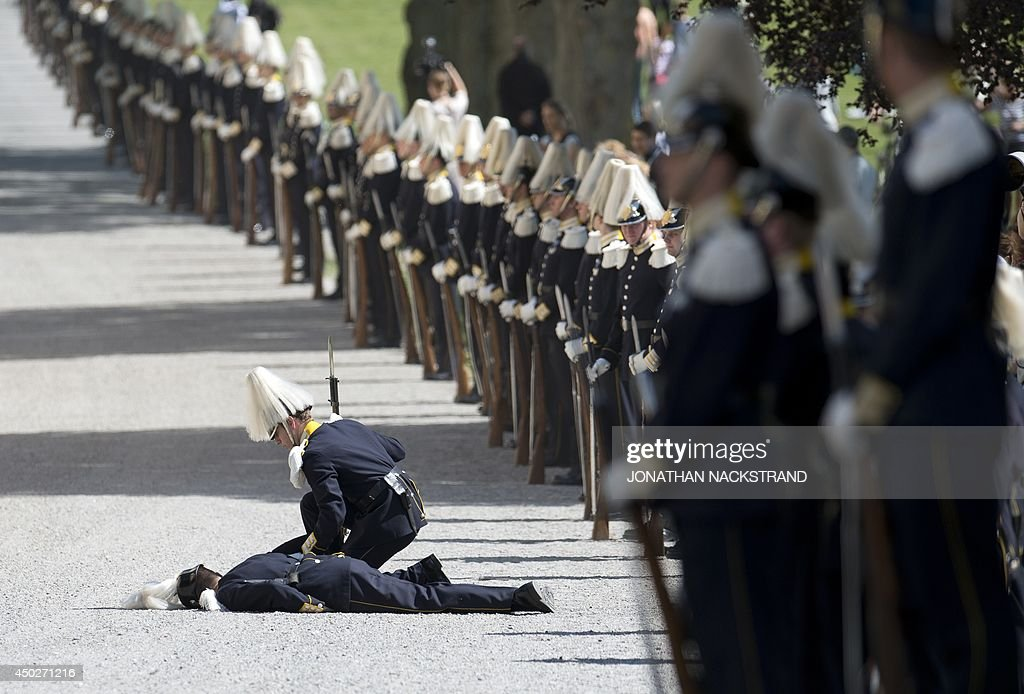 A soldier from the royal guard lies on the ground after fainting during guests arrival for Princess Leonore's christening on June 8, 2014 at the Royal Chapel in Drottningholm's royal palace near Stockholm.