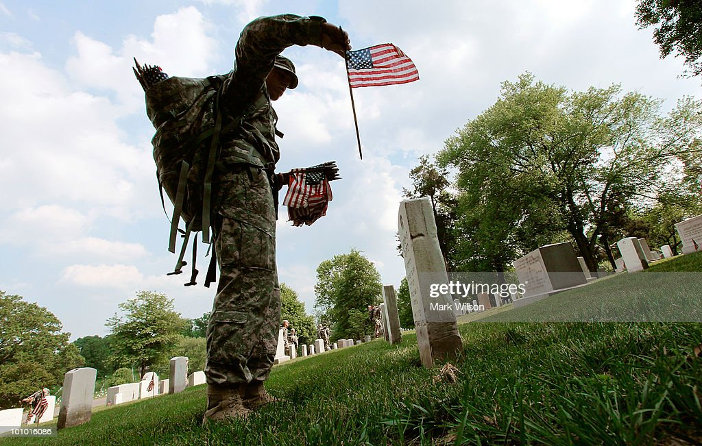 A soldier from the U.S. Army Old Guard places a flag on a grave at Arlington National Cemetery May 27, 2010 in Arlington, Virginia. About 1,300 soldiers, sailors and Marines in about three hours placed a flag at each of the more than 300,000 gravestones at Arlington ahead of the Memorial Day weekend.