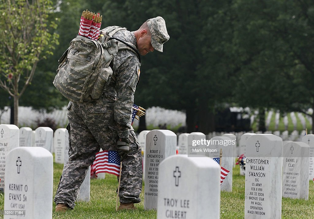 A soldier from the U.S. Army Old Guard places a flag on a grave at Arlington National Cemetery May 27, 2010 in Arlington, Virginia. It took 1,300 soldiers, sailors and Marines about three hours to place a flag at each of the more than 300,000 gravestones at Arlington ahead of the Memorial Day weekend.