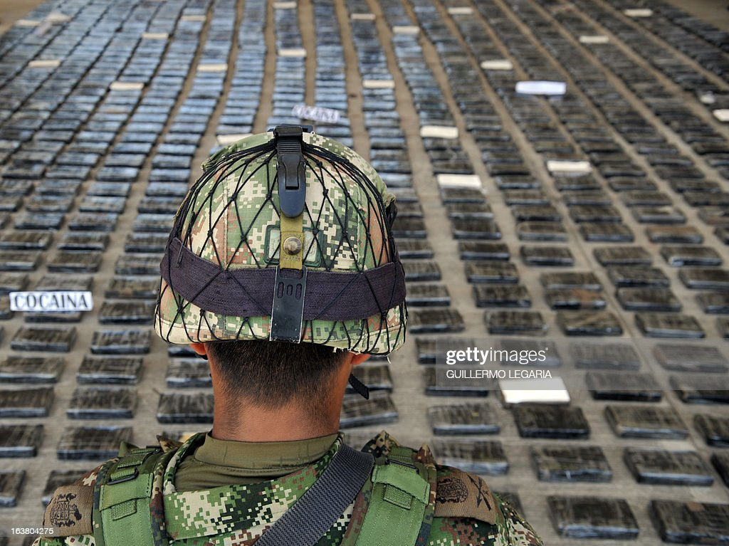A soldier guards a shipment of 3,9 tons of cocaine seized in a large clandestine laboratory for the production of the drug, during its presentation to the press on March 16, 2013, at the military air base in Tumaco, Narino department, Colombia. Soldiers from special counternarcotics brigade found and destroyed on 13 March, in the municipality of Timbiqui, Cauca deparment, a huget laboratory to produce cocaine, considered by authorities as the largest collection center for alkaloids processing of the Revolutionary Armed Forces of Colombia (FARC) and from which drug was sent to Central and North America, officials said. AFP PHOTO/Guillermo Legaria