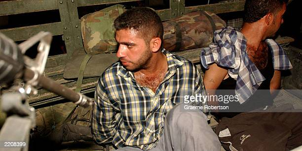 S soldier guards two Iraqi men arrested for allegedly creating couneterfeit Iraqi money July 26 2003 in Baghdad Iraq US soldiers raided the home at...