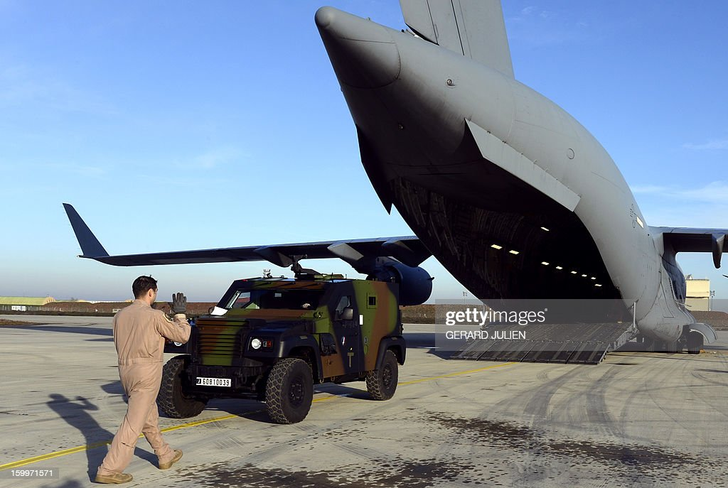 A US soldier guides a French armored vehicle climbing aboard a C17 aircraft of the US Airforce carriying French armoured vehicles at the Istres military airport (BA 125) on January 24, 2012 in Istres, southern France, prior to take off and heading toward Mali as part of the 'Serval' operation.
