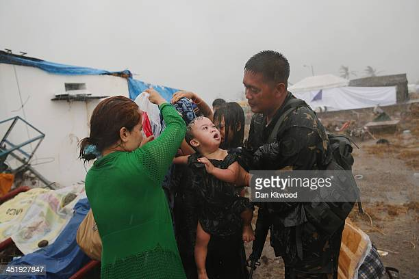 A soldier helps a family cover a baby during a torrential rain storm at Taclaban airport on November 14 2013 in Leyte Philippines Typhoon Haiyan...