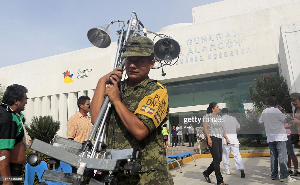 A soldier helps in the evacuation of the Alarcon Hospital in Acapulco after a 5.62-magnitude aftershock which was reported minutes after a 6.0 magnitude earthquake shook Mexico City on August 21, 2013. A strong 6.0 magnitude earthquake and an aftershock rattled Mexico on Wednesday, causing evacuations of buildings in the capital and hotels in the Pacific resort of Acapulco. The quake's epicenter has been located 17 km west of the town of San Marcos in the southern state of Guerrero, the National Seismology Center said. A 5.62-magnitude aftershock was reported 20 minutes later 14 km northeast of Acapulco, where rocks from a hill rolled into a street and some hotel facades showed cracks while tourists poured into the streets. AFP PHOTO / Pedro PARDO
