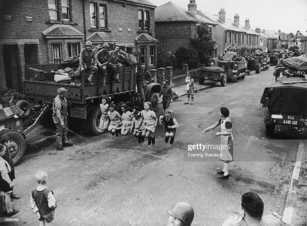 A US soldier helps some children with their skipping. He is watched by his comrades in a town street in the south of England, lined with equipment awaiting shipment to France.