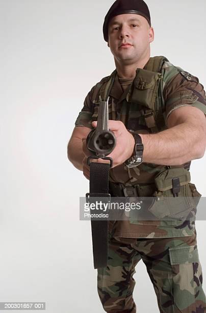 Soldier holding grenade launcher, portrait