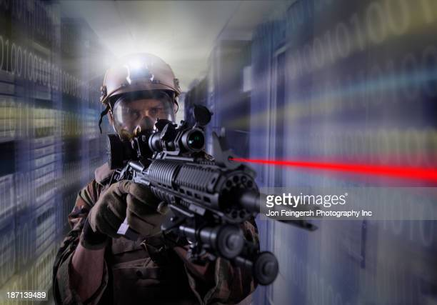 Soldier holding gun in server room