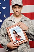 Soldier holding photograph of family by American flag