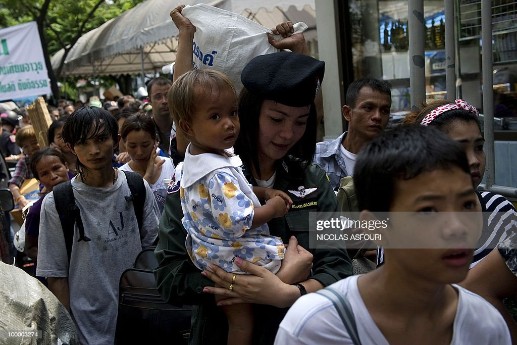 A soldier (C) holds a baby as ''Red Shirt'' anti-government protester leave a temple which had been turned into a shelter within an anti-government protest site in downtown Bangkok on May 20, 2010. Gunshots rang out near a Buddhist temple in the heart of an anti-government protest zone in Bangkok, and soldiers were advancing on foot along an elevated train track, an AFP photographer saw. Thai security forces stormed the 'Red Shirts' protest camp on May 19 in a bloody assault that forced the surrender of the movement's leaders who asked their supporters to disperse. AFP PHOTO/ Nicolas ASFOURI