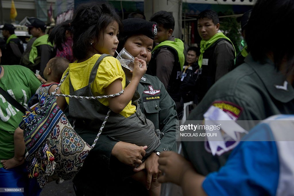 A soldier (C) holds a girl as ''Red Shirt'' anti-government protesters leave a temple which had been turned into a shelter within an anti-government protest site in downtown Bangkok on May 20, 2010. Gunshots rang out near a Buddhist temple in the heart of an anti-government protest zone in Bangkok, and soldiers were advancing on foot along an elevated train track, an AFP photographer saw. Thai security forces stormed the 'Red Shirts' protest camp on May 19 in a bloody assault that forced the surrender of the movement's leaders who asked their supporters to disperse. AFP PHOTO/ Nicolas ASFOURI