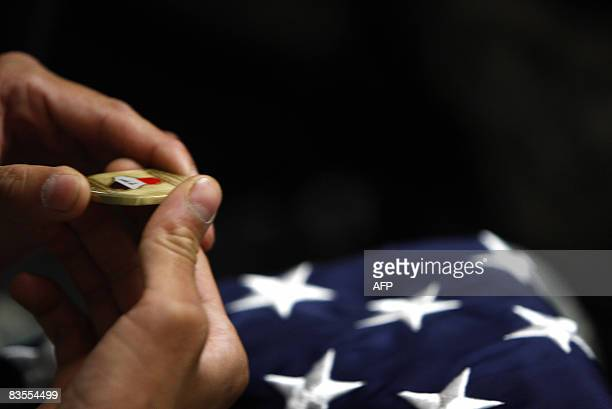 A US soldier holds a medal with the map of Iraq and a folded US flag following the US Citizen Naturalization ceremony at Camp Victory in Baghdad on...