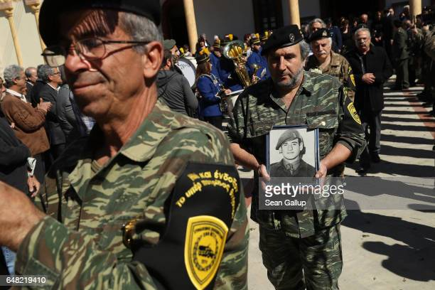 A soldier holds a portrait of Georgiou Theodoulos Theodoulou at Theodoulou's funeral following an Orthodox service on March 5 2017 in Pera Chorio...