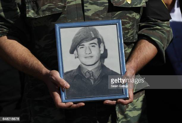 A soldier holds a portrait of Georgiou Theodoulos Theodoulou at his funeral on March 5 2017 in Pera Chorio Nisou Cyprus Theodoulou was an 18yearold...