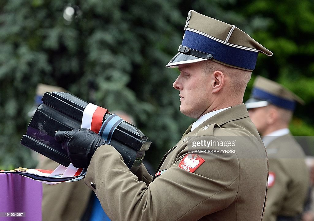 A soldier holds an urn bearing the ashes of Poland's late communist leader, General Wojciech Jaruzelski, during his burial ceremony at Warsaw's Powazki military cemetery on May 30, 2014. Jaruzelski, Poland's last communist leader, who died on May 25, 2014 aged 90, was laid to rest in Warsaw at a state funeral, but no day of national mourning was called for the controversial figure who divides Poles even in death.