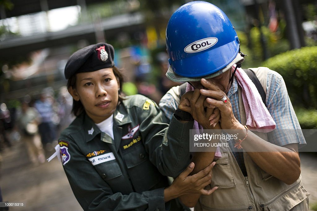A soldier (L) holds the hand of a ''Red Shirt'' anti-government protester as he leaves a temple which had been turned into a shelter within an anti-government protest site in downtown Bangkok on May 20, 2010. Gunshots rang out near a Buddhist temple in the heart of an anti-government protest zone in Bangkok, and soldiers were advancing on foot along an elevated train track, an AFP photographer saw. Thai security forces stormed the 'Red Shirts' protest camp on May 19 in a bloody assault that forced the surrender of the movement's leaders who asked their supporters to disperse.