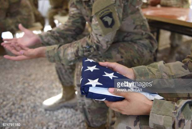 US soldier holds the national flag ahead of a handover ceremony at Leatherneck Camp in Lashkar Gah in the Afghan province of Helmand on April 29 2017...