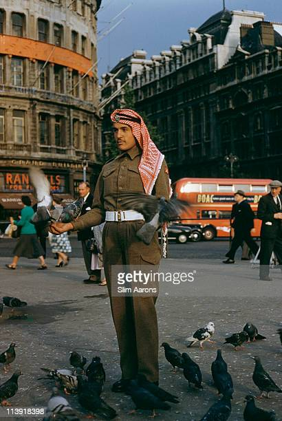 A soldier in a middle eastern military uniform feeding the pigeons in Leicester Square London 1955