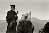 Soldier in front of the Albanian flag guarding the statue of 'Mother Albania'on the outskirts of Tirana is dedicated to the Partisans of WWII On it...
