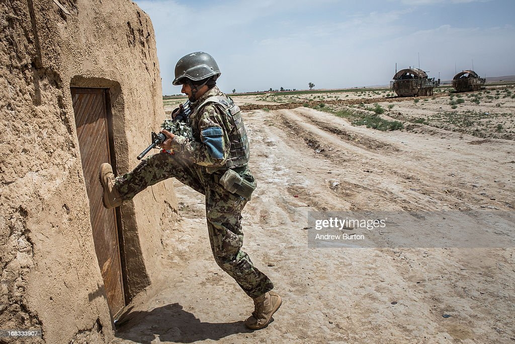 A soldier in the Afghan National Army's 6th Kandak (battalion), 3rd company kicks down a door during a joint patrol with the U.S. Army's 1st Battalion, 36th Infantry Regiment near Command Outpost Pa'in Kalay on April 6, 2013 in Kandahar Province, Maiwand District, Afghanistan. The United States military and its allies are in the midst of training and transitioning power to the Afghan National Security Forces in order to withdraw from the country by 2014.