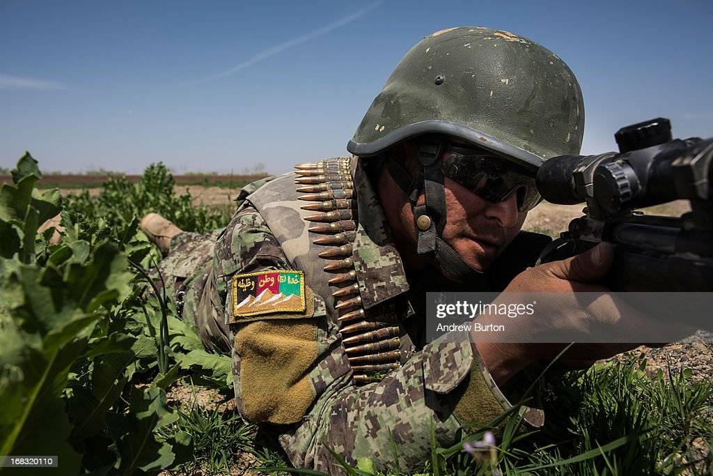 A soldier in the Afghan National Army's 6th Kandak (Battalion) aims his weapon during a joint patrol with United States forces, after an improvised explosive device (IED) hit a United States vehicle, near Command Outpost Azim-Jan-Kariz, on March 17, 2013 in Kandahar Province, Maiwand District, Afghanistan. No one was seriously injured in the blast. The United States military and its allies are in the midst of training and transitioning power to the Afghan National Security Forces in order to withdraw from the country by 2014.